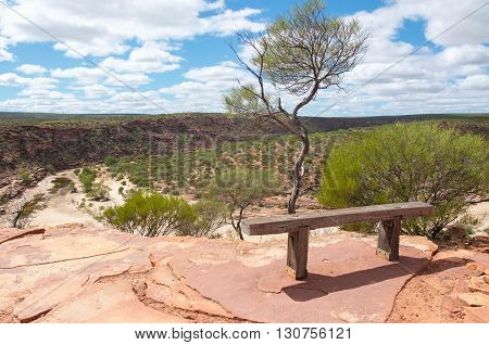 Peaceful meditation bench on a red sandstone bluff overlooking the Murchison River gorge with native plants in Kalbarri National Park in Western Australia.