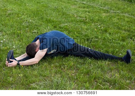 Outdoor yoga workout. Young man doing an exercise in the city park bending forward touching the knee with the head