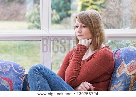 Lonely young redhead woman is sitting on the sofa in conservatory and she is looking ahead.