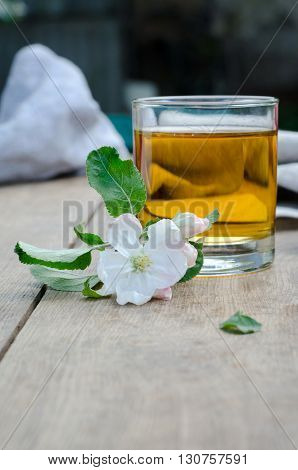Apple juice and flowers of apple trees on a wooden table