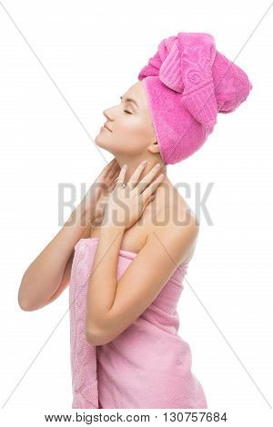 Beautiful young woman with hair and body wrapped in pink towel. Isolated over white background. Copy space.