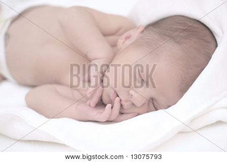A very young (a week old) baby is sleeping and sucking his small lovely fingers. The image is soft and dominated by whites and light tones.