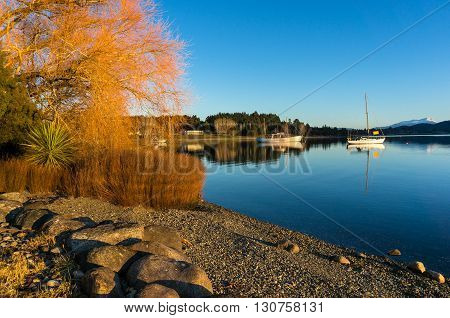 Lake Te Anau on dawn. Evening landscape with calm lake and boats. Te Anau Fiorland South Island New Zealand