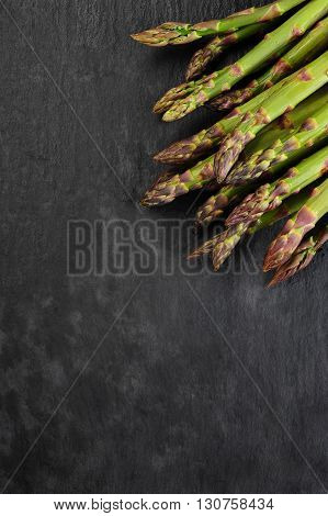 fresh green asparagus over black slater background