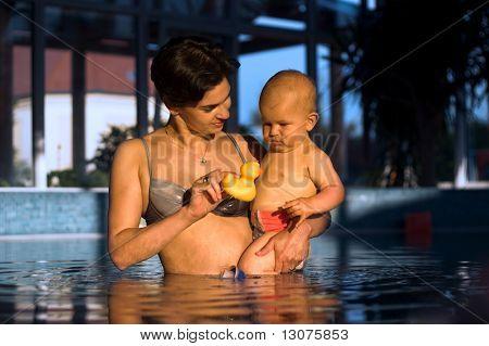 Baby und seine Mutter sind in einer sehr intimen Moment. Sie sind ein Bad im Pool nehmen und spielen, um