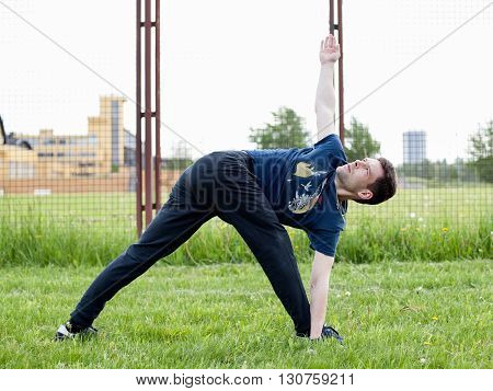 Outdoor yoga workout. Young man doing an exercise in the city park turning triangle pose