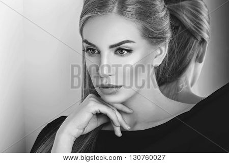 Beautiful young woman with blond hair and makeup covered with piece of black fabric. Copy space.