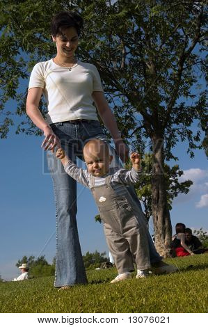 A one year old baby and his mom are spending some time together outdoor. The baby is practicing how to walk.