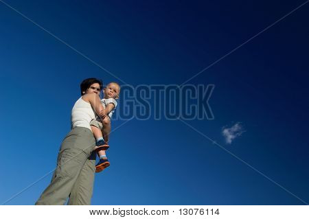A one year old baby and his mom are spending some time together outdoor. The background is the clear blue sky.
