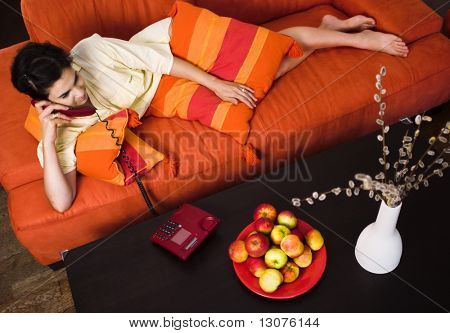 Young women is resting on the couch and receiving a phone call.