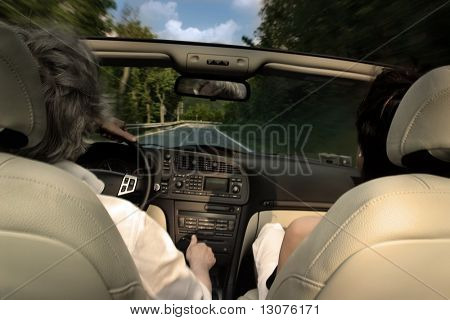 Az older couple are travelling by a cabrio car.