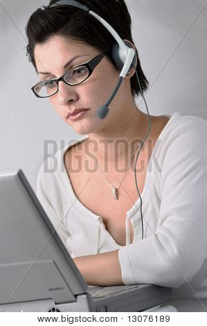 Beautiful young woman with charming big green eyes is bearing modern glasses and receiving calls on a headset.