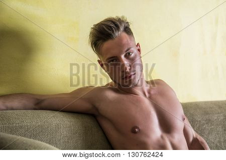 Shirtless sexy young man in panties relaxing on couch and looking