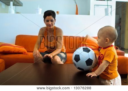 Baby is playing with a real soccer ball indoor.