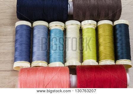 Several spools of thread of different colors and sizes on a wooden table