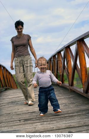 One year old baby and his mom are walking on a footbridge.