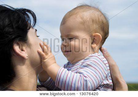 Um momento muito íntimo: um bebê de um ano de idade fondles de sua mãe.