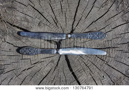 two old knives on grey beam cut close up