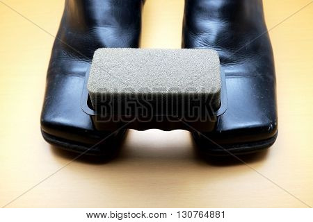 Shoe polishing brush and black leather shoe on wooden floor. Space for texts.