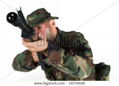 Soldier is aiming. The focus is placed to the muzzle while the man himself is out of focus in anonymity.