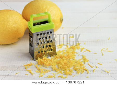 Peeling lemon zest. Small grater, citrus fruit, yellow, zest cuttings, white table. Close-up, soft focus.