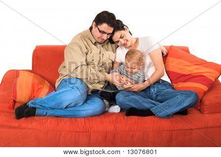 Eine Familie von einem Kleinkind-Sohn, Mutter und Vater sitzen auf der Couch zusammen zu Hause. Sie sind