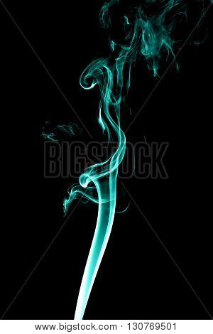 Cyan smoke on black background from the incense sticks