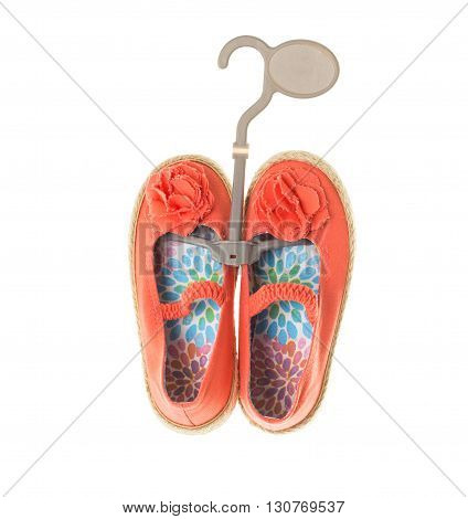 Baby girl orange fabric sneakers with floral ornament and straw sole on plastic hanger. Isolated on a white background.