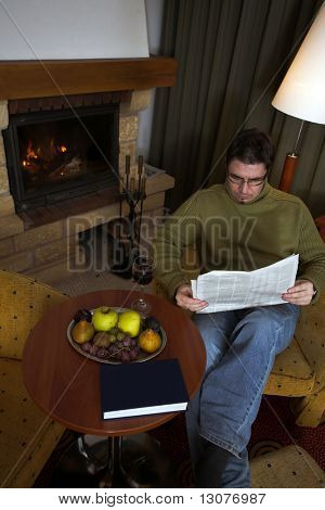 Man is reading the newspaper in front of the fireplace and enjoys the comfort of his home.