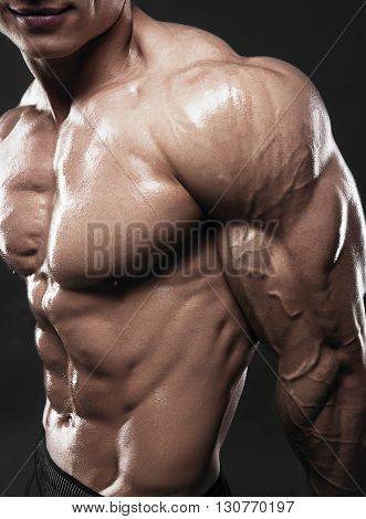 Bodybuilder showing his biceps muscles, personal fitness trainer. Strong man flexing his muscles
