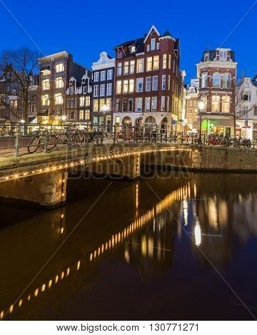AMSTERDAM NETHERLANDS - 16TH FEBRUARY 2016: A view along the Keizersgracht canal in Amsterdam at night. Buildings bridges and bikes can be seen.