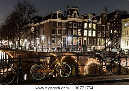 AMSTERDAM NETHERLANDS - 17TH FEBRUARY 2016: Bridges buildings and bikes at the Leidsegracht and Keizersgracht canal intersection in Amsterdam at night.