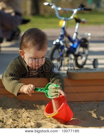 Young boy is playing outdoor in a sand pit.
