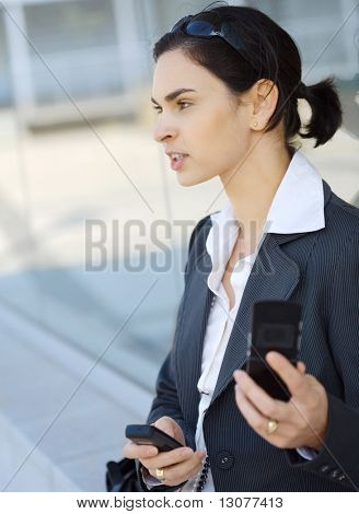 Young businesswoman is using two mobile phones at the some time. She is outdoor, somewhere in the downtown district.