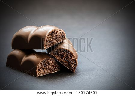 part porous chocolate close-up on a dark background