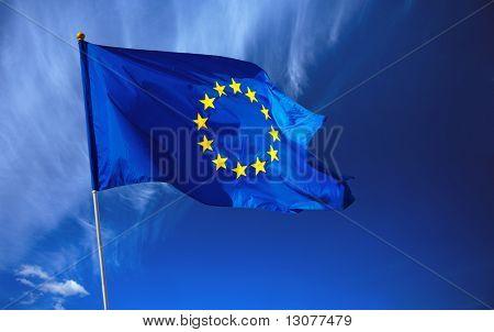 Bandera de la Unión Europea ante el cielo azul profundo.