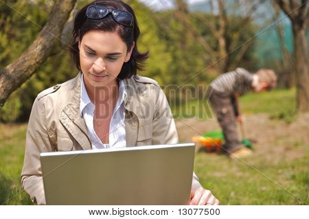 Attractive young mother is sitting on the ground in the garden and using a laptop while a 5 years old boy is playing in the background.