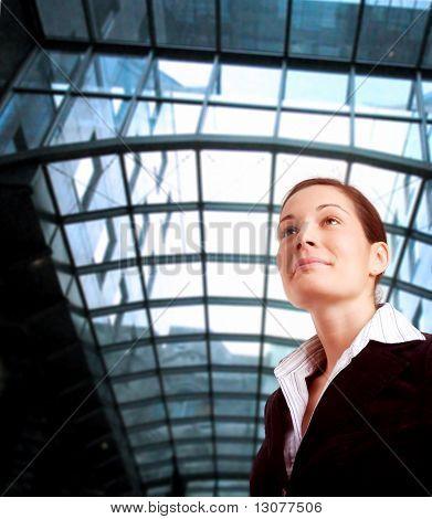 Joven y ambiciosa empresaria mira el futuro frente a un edificio de oficinas.