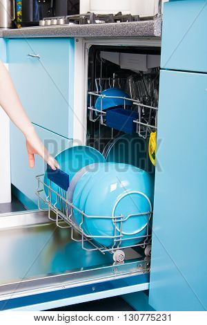 Woman Empty Out The Dishwasher