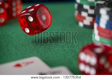 Red casino dice rolls and casino chips on green table