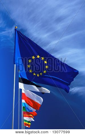 Flag of the european union and some nations in front of the deep blue sky.