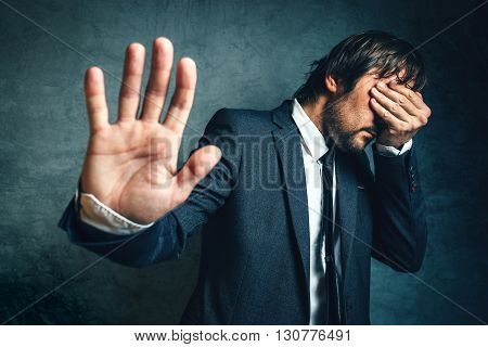 Stressed businessman after business project failure covering eyes in despair and hand gesturing stop to camera.