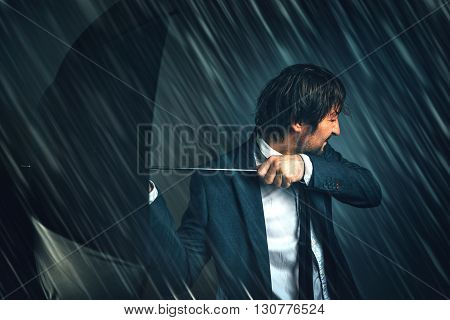 Business challenge and difficulties concept with businessman standing in rain storm with open umbrella