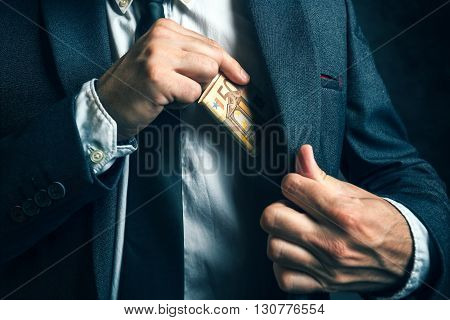 Money in pocket businessman putting euro banknotes in suit pocket bribe and corrupution concept.