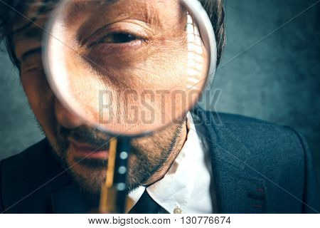 Enlarged eye of tax inspector looking through magnifying glass inspecting offshore company financial papers documents and reports.