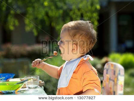 Two years old baby boy eating. Family BBQ party outdoor, in the garden.