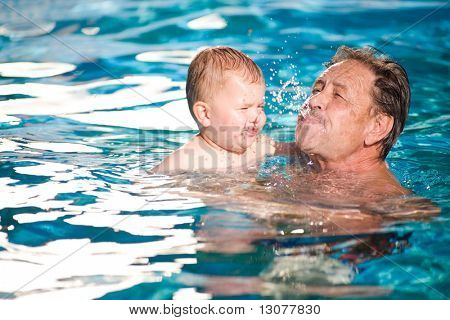 Grandfather and grandson playing together in the pool. Outdoor, summer.
