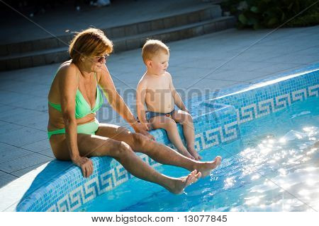Grandmother and two years old grandson enjoy water and sunshine on the poolside. Natural light, summer.