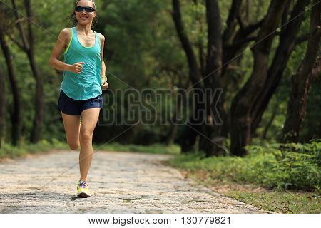 young fitness woman trail runner running in forest