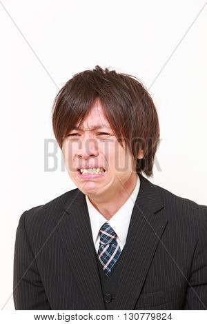 portrait of sad young Japanese businessman on white background